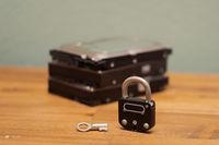Computer hard disks and metal padlock symbolizing concept for encrypted data, cyber security on wooden desk