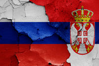 flags of Russia and Serbia painted on cracked wall