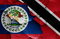 flags of Belize and Trinidad and Tobago painted on cracked wall