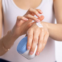 Woman applying hand cream to moisturize skin - stock photo