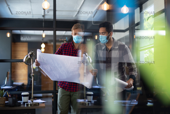Diverse male colleagues wearing masks in disucssion holding architectural plans in office