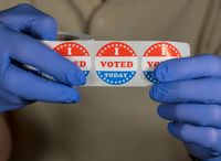 Gloved hands holding roll of I Voted Today stickers or buttons ready for voter who voted in person in election