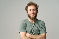 Young handsome man with beard and curly hair in olive t-shirt looking at camera isolated on white background. Portrait of smiling young man with hands folded