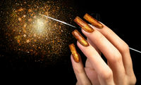 Hand with gold manicure and a brush on a black background covered with sparkles. Nail design. Extended nails.