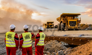 Large Dump Trucks transporting Platinum ore for processing with mining safety inspectors in the foreground