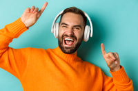 Close-up of handsome modern man listening music in headphones, standing in orange sweater over turquoise background