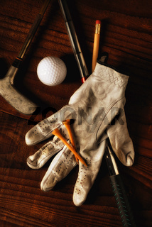 A golf glove and antique golf clubs, golf ball abd tees on a rustic wood surface.