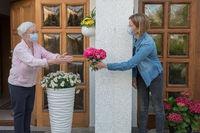 Seniorin mit Mundschutz bekommt Blumen von Nachbarin mit Mundschutz