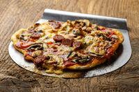 Pizza mit Heber auf Holz