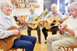 Gruppe Senioren lernt Gitarre spielen zusammen in einem Gitarrenkurs im Altersheim