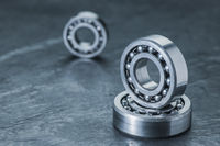 Three spherical roller bearings on slate near