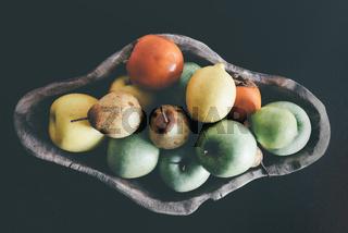 organic fruits in wooden bowl on dark table background