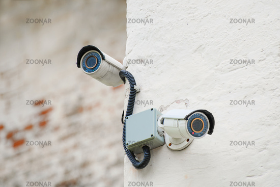 surveillance cameras on the wall of a building with a shallow depth of field