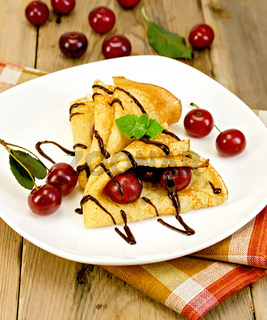 Pancakes with cherry and chocolate syrup with a napkin