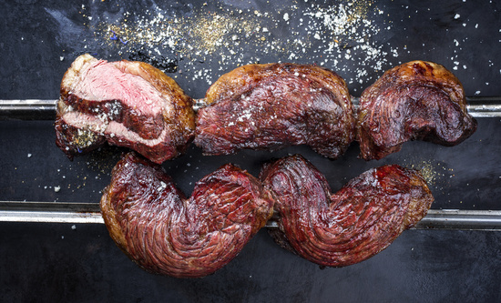 Barbecue dry aged wagyu Brazilian picanha from the sirloin cap of rump beef sliced and offered as top view on a skewer on a rustic old board