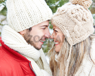 Paar im Schnee im Winter lacht sicht an