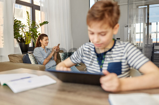 mother with smartphone and son learning at home