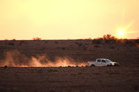 car on a dusty unsealed road in sunset light mood
