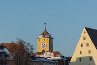 The famous old town hall tower of the bavarian town Regensburg on sunny winter morning with snow and ice