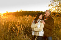 Couple hugging during autumn sunset countryside