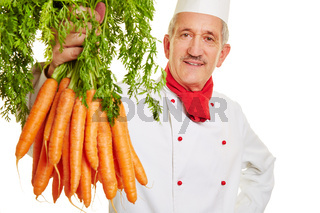 Koch hält Bund Möhren hoch