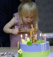 Little girl enjoying her birthday cake with candy