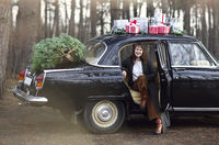 Stylish woman preparing Christmas presents and tree for celebration