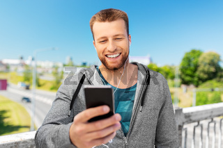 smiling young man with earphones and smartphone