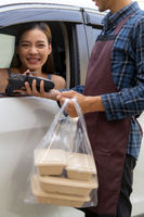 Asian woman making contactless payment with credit card for take out drive thru food