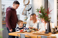 Parents with son and sister in kitchen during Christmas holidays