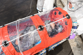 Biohazard team with virus patient in stretcher