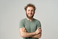 Handsome young man with curly hair in olive t-shirt looking at camera isolated on white background. Portrait of smiling young man with hands folded