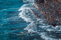 Photo of beautiful clear turquoise sea ocean water surface with ripples and bright splash on stone seascape background, horizontal picture