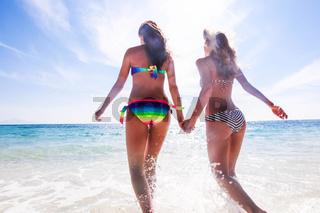Women in bikni run to sea