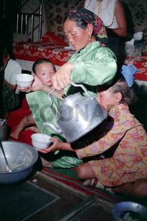 In der Jurte einer Aratenfamilie in der Wüste Gobi, eine Mutter gießt ihren Kindern Buttertee ein,  Foto von 1977