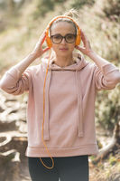 Portrait of beautiful sports woman wearing sunglasses, hoodie and headphones during outdoors training session