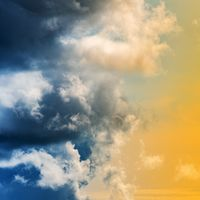 Dramatic blue thunderclouds and stunning yellow-golden fluffy clouds
