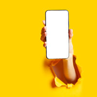 Woman hand in the paper hole holding smartphone. Mobile application.