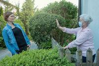 Seniorin mit Mundschutz hält Sicherheitsabstand zur Nachbarin