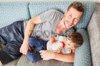 Glücklicher Vater beim Flasche geben mit seinem Sohn