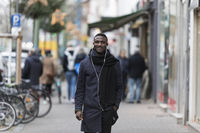 Young Black Man Walking Happily in City Smiling