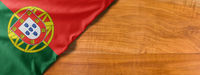 National flag of Portugal on a wooden background with copy space