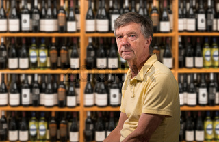 Senior caucasian man sitting in his wine cellar full of bottles
