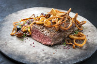 Traditional dry aged sliced roast beef with fried onion rings and potatoes served as closeup on a modern design plate