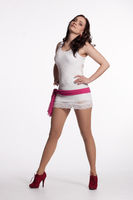 Young woman in a white mini dress, red heels with pink scarf