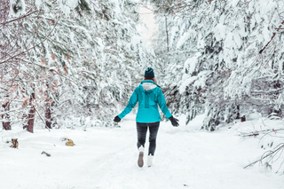 Woman walking in a snow covered forest