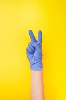 Sign victory made female's hand in rubber protective glove.