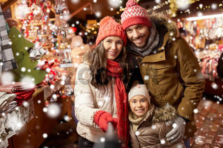 happy family taking selfie at christmas market
