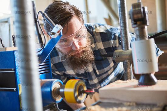 Tischler mit Schutzbrille beim Bohren von Holz