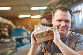 Schreiner Lehrling trägt Balken aus Holz